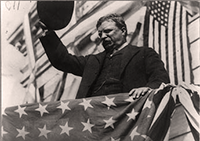 Theodore Roosevelt tips his hat to the crowd on the campaign trail