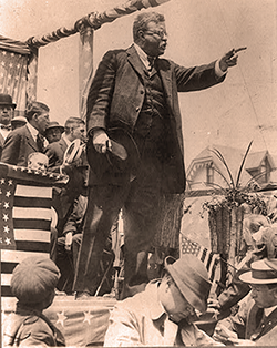 Theodore Roosevelt on a campaign platform, holding his hat in his hand
