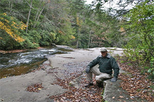 Photograph of Offutt Johnson relaxing on the Edison sitting/thinking stone in the Fall of 2012 at Swallow Falls State Park.