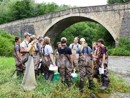 A group of kids and teacher standing in waders in front of a stone bridge at a stream.