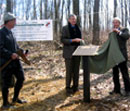 Francis Zumbrun looks on while John Garrett and Kirk P. Rodgers unveil the Centennial Plaque at the Garrett-Potomac State Forest