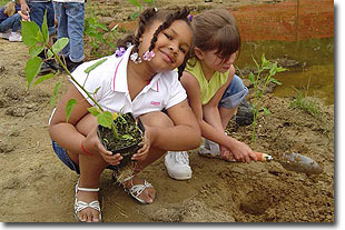 2 young girls planting native plants in their school yard
