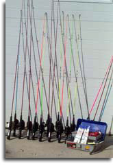 A tacklebox and many fishingrods leaning against a wall.