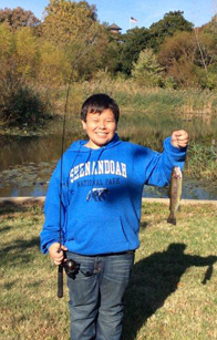 Photo of a kid holding a rainbow trout
