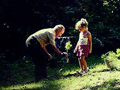 Grandfather with grandaughter planting a small tree