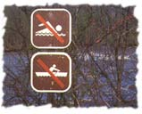 [Signs for no swimming and no boating in front of a river.]