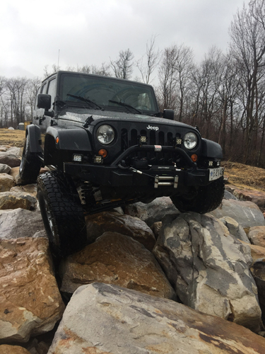 A jeep sitting on rocks.