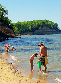 Family fossil hunting on beach in Calvert Cliffs State Park