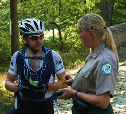 A ranger at Fair Hill assists a cyclist