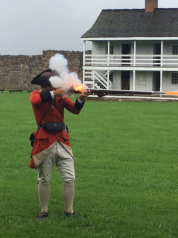 A person dressed as a solider and firing a musket.