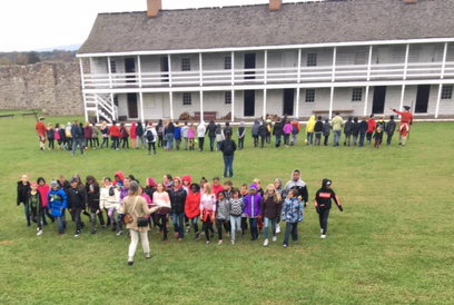 Two groups of people standing outside one of teh buildings ar Fort Frederick.