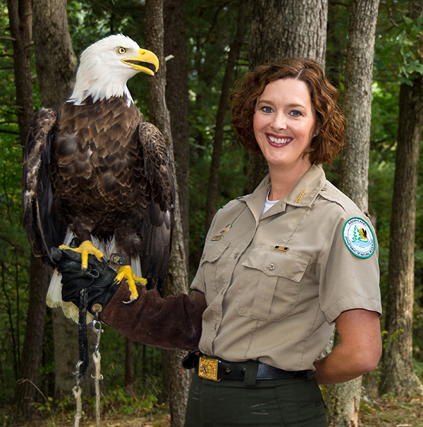 A park ranger standing outside in the summer holding a large bald eagle on her arm.