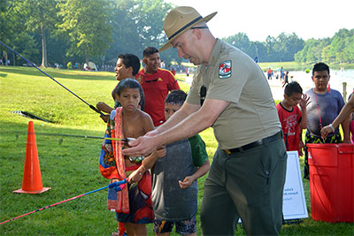 A Park ranger showing kids how to fish.