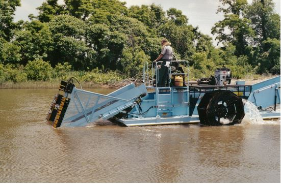 A person on a harvesting machine in the water.